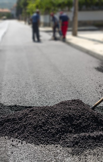 Workers on new road. Heap with asphalt. photo