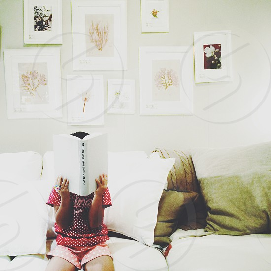 girl in red and white polka dot t shirt reading a book photo