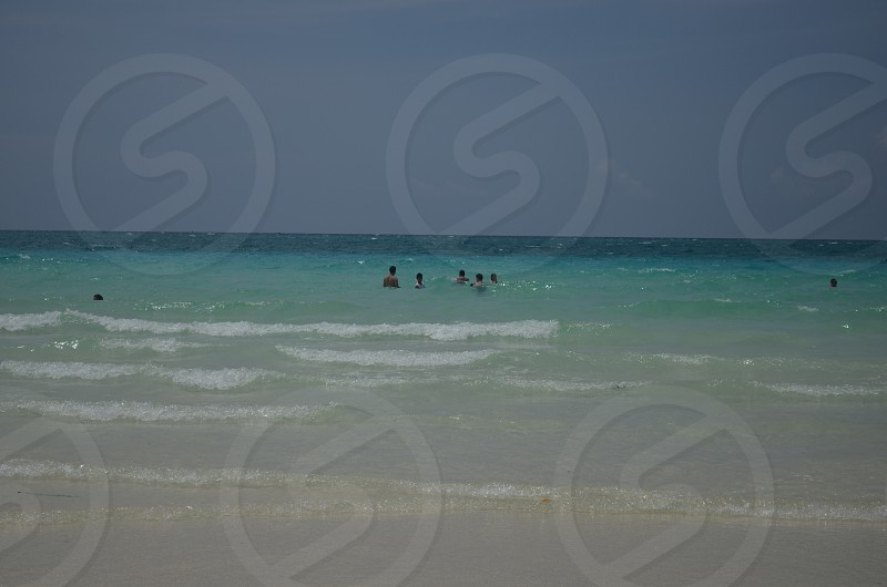 group of people on sea under stratus clouds photo