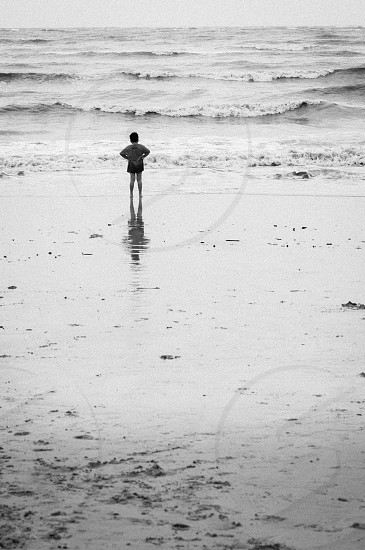 Lone boy standing on the beach. Black and white high speed film grain effect. photo