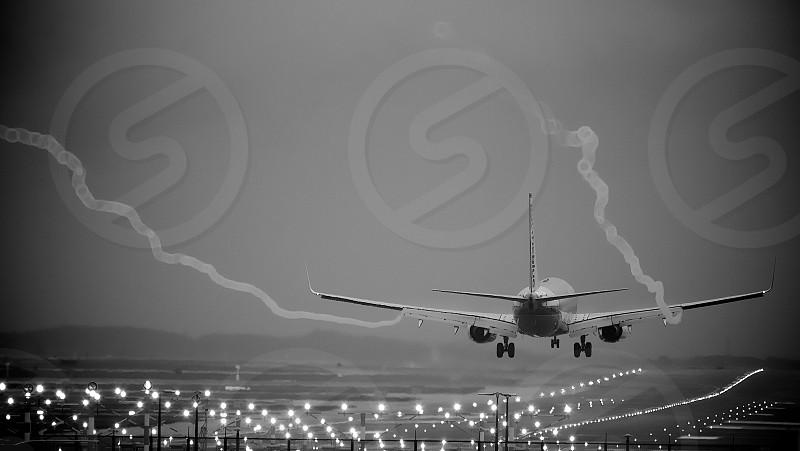 Aircraft landing on rainy day with wingtip vortices . landing runway wet rainy blackandwhite mono black white vortex vortices flying airplane aeroplane aircraft touchdown  photo