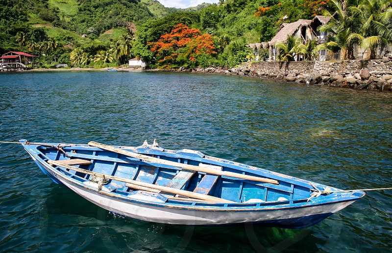 Rowboat anchored off tropical island photo