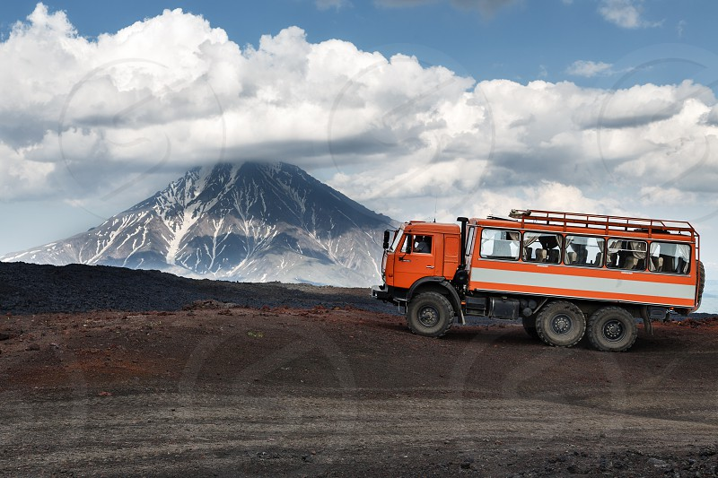 KAMCHATKA RUSSIA - JUNE 24 2016: Russian expedition truck KamAZ (6-wheel drive) on mountain road on background of lava fields and beautiful volcano. Eurasia Russian Federation Far East Kamchatka Peninsula Klyuchevskaya Group of Volcanoes. photo