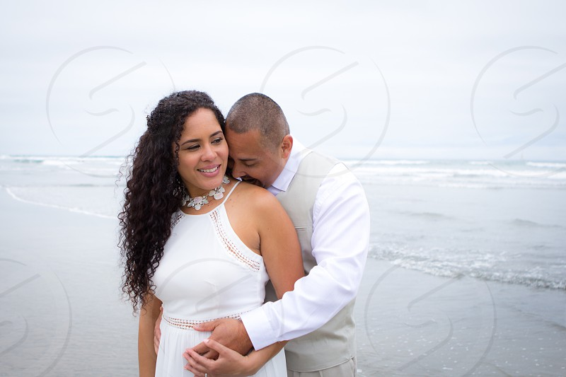 woman in black long curly black hair wearing white collar necklace and white halter neck dress hugged by man in grey vest over white dress shirt standing at the beach with mild sea water under white sky photo