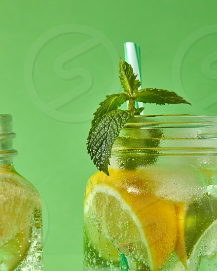 A close-up of a sprig of green mint in focus in a glass jar with cold natural handmade lemonade on green background. Concept of cold alcoholic or non-alcoholic summer drinks. photo