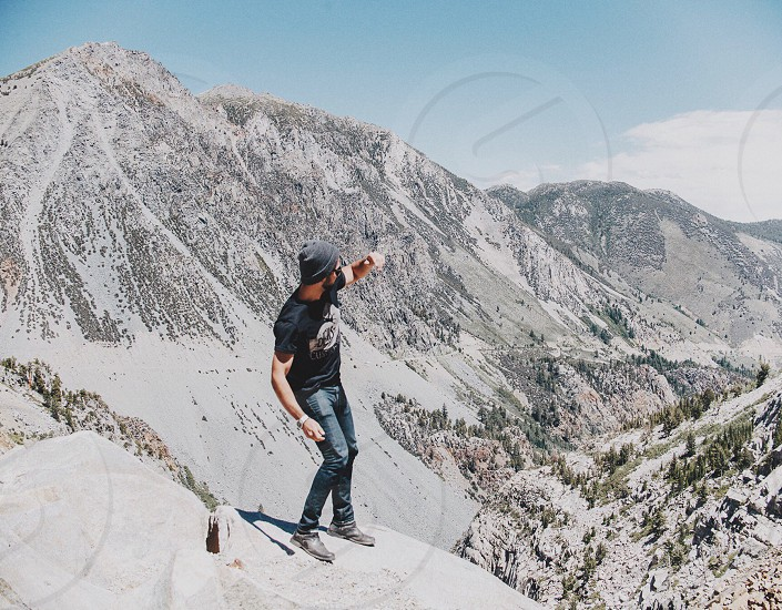 man standing on rocky cliff with rocky mountain on background photo