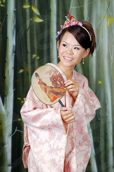 woman in oink kimono holding paper fan photo