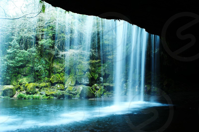 water falls cascading down river in front of cave mouth photo