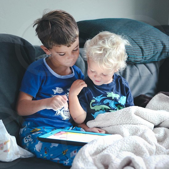 2 children using tablet on gray textile covered bed with white bed comforter photo