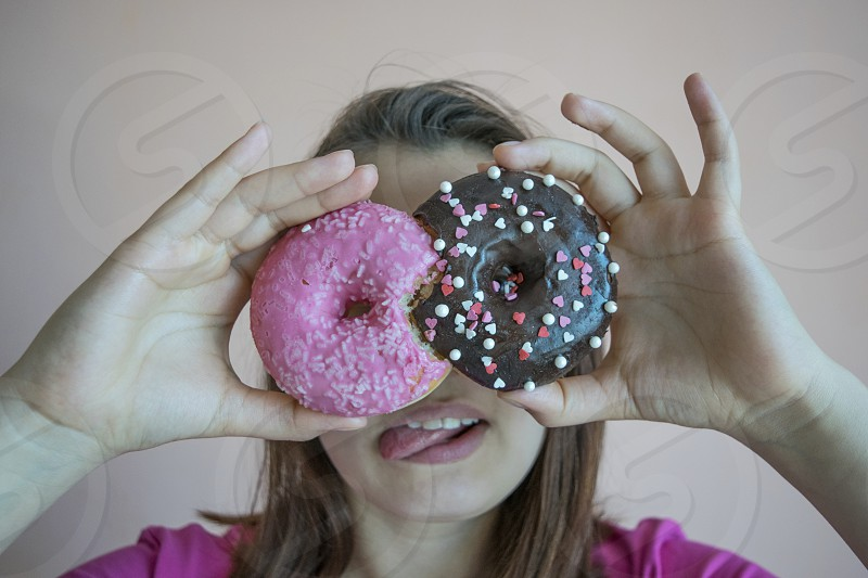 Portrait of unidentified happy girl in pink t-shirt holding donuts at eyes and showing tongue  photo