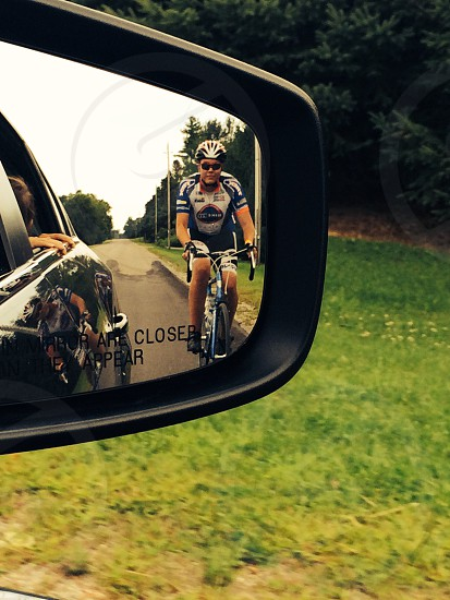 reflection of cyclist on side mirror at daytime photo