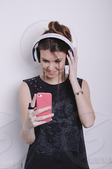 woman in black crew neck sleeveless shirt wearing black and white headphones photo