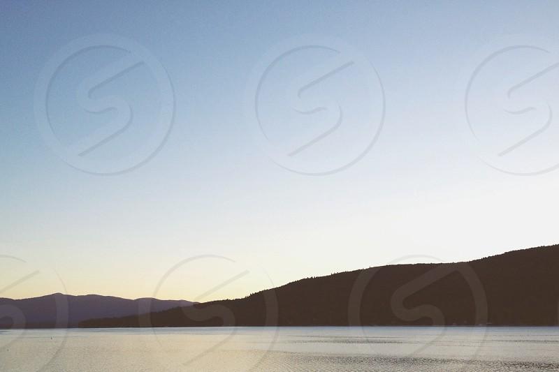 mountain across ocean photography  photo