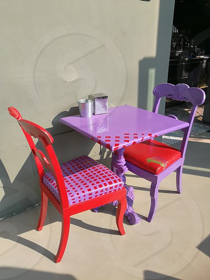 purple and red wooden table with chair outside photo