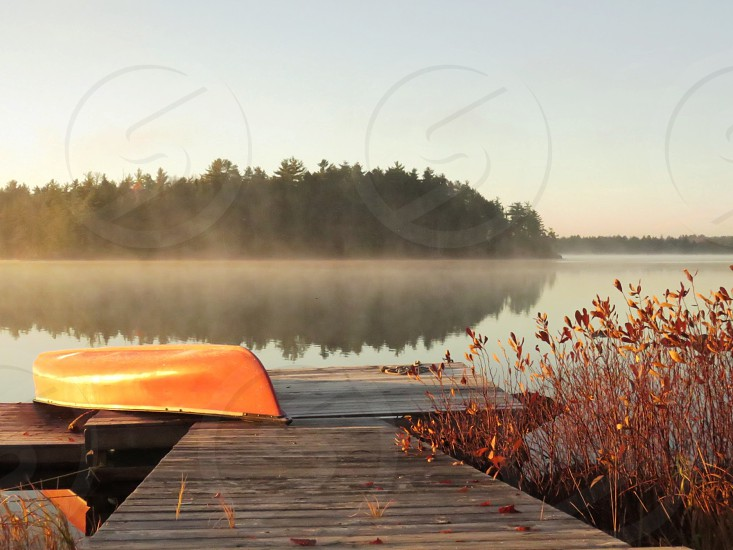 Red canoe awaits. As the morning mist rises the island comes into view from the dock. photo