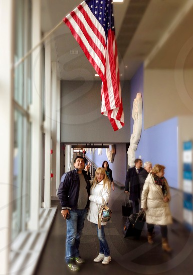 A couple of tourists at the airport crossing in New York are happy with the arrival and are photographed against the background of the American flag. photo