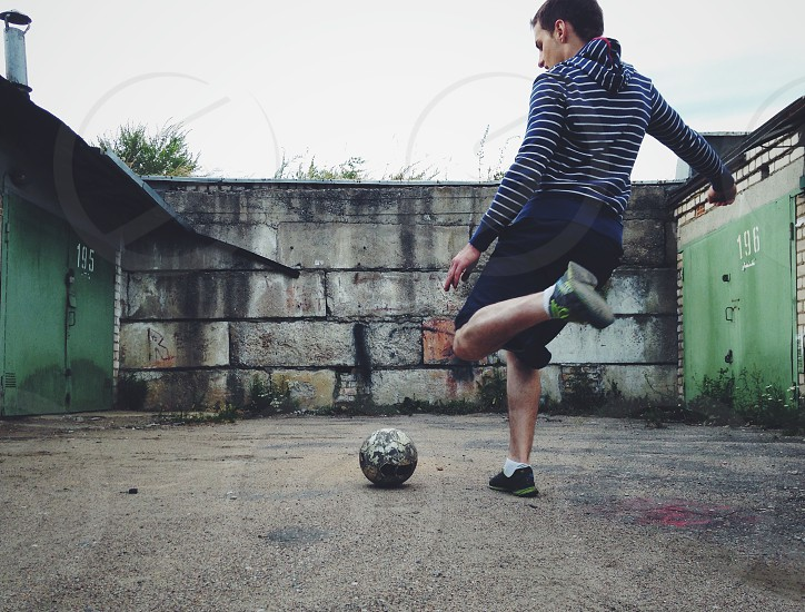 man in blue and white striped hoodie about to kick soccer ball towards grey concrete wall photo
