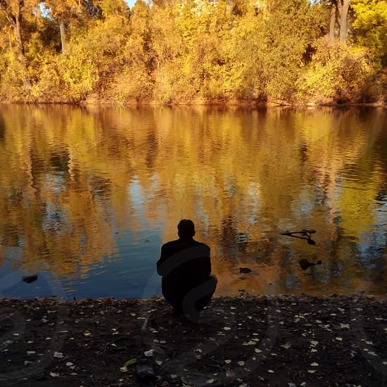 man standing beside lake photo