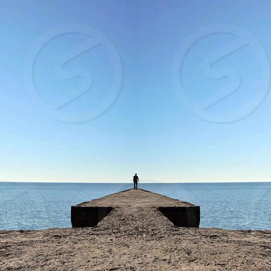 person standing at the edge of the sailboat dock photo