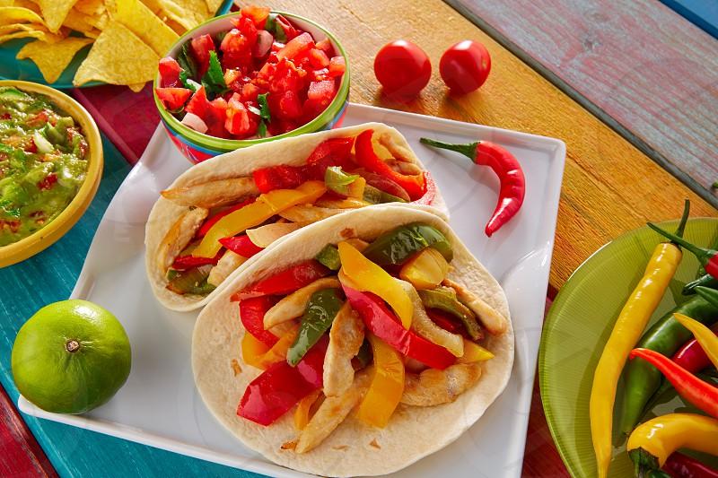 Chicken fajitas tacos mexican food guacamole pico de gallo chili peppes sauces photo