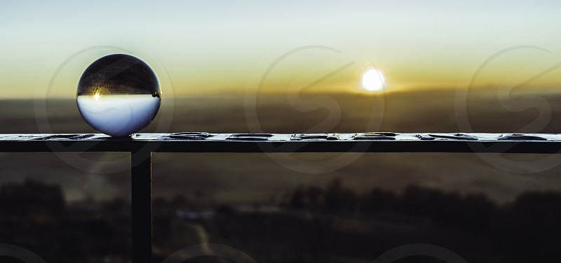 Crystal ball on the railing reflecting the sky and the sunrise sun photo