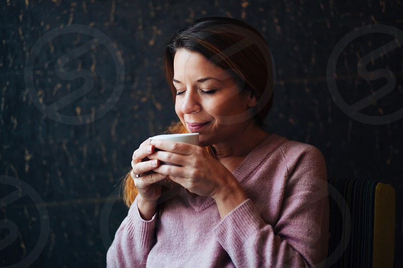 Portrait of a young woman enjoying drinking coffee photo