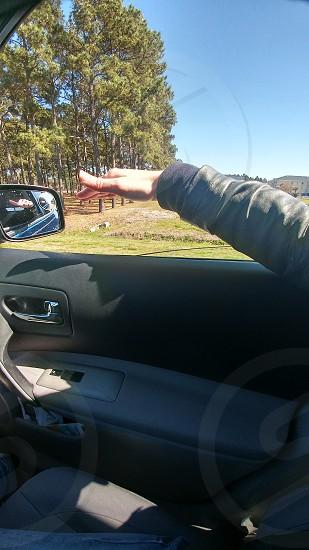hand waving in wind outside through car window photo