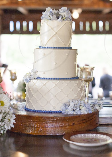 Wedding cake trimmed with hydrangeas a on wooden block photo