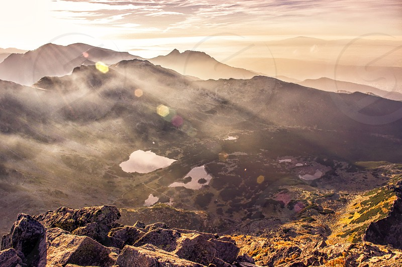 Mountain landscape with lens flare and sun coming from behind the mountains. Tatras Poland photo