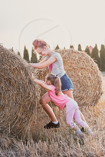 Sisters teenage girl and her younger sister pushing hay bale playing together outdoors in the countryside. Candid people real moments authentic situations photo