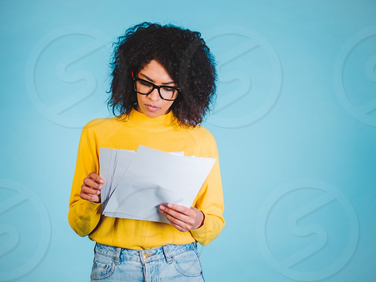 Education and business concept - international student studying in college. Or modern african american businesswoman with afro hairstyle reading documents on blue background in studio. photo