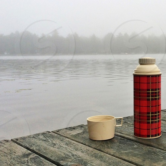 red and beige thermos on wooden deck with foggy weather view photo