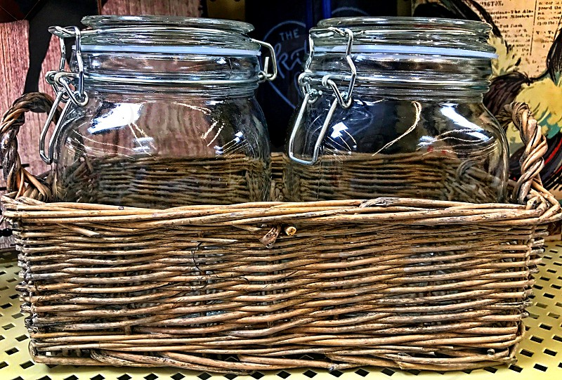 Two glass mason jars sit in a basket photo
