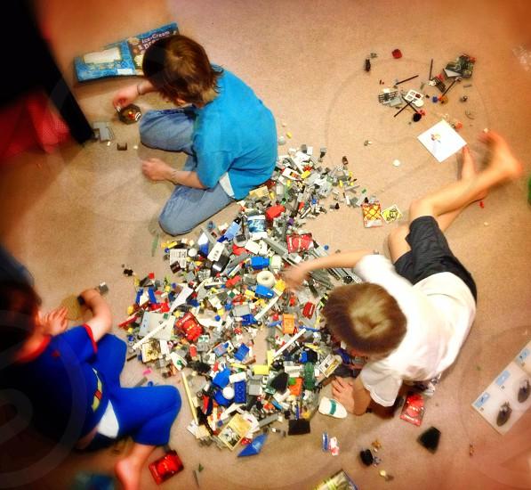 three boys playing lego toys photo