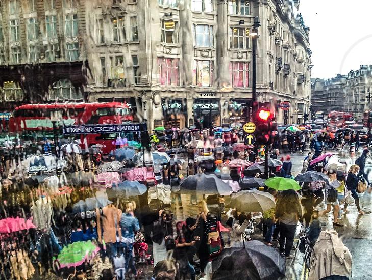 Rain rainy weather umbrella  umbrellas people street streets city city life crowded crowd bus viewLondon England grey wet dripping drops bus Oxford circus Oxford street photo