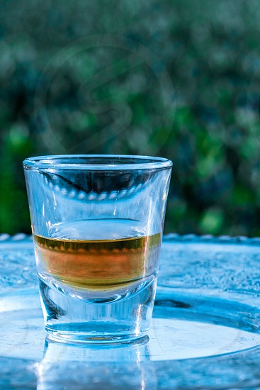 Glass of whiskey sitting on a tray outdoors in front of a field. Editing to have cool tone colors. photo