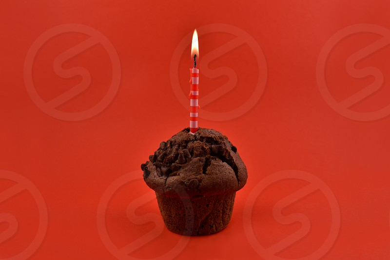 Chocolate muffin with candle. Muffins on a red background. Birthday muffin with cake candle photo