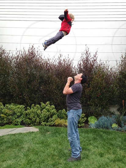Baby kid child boy man father toss throw above up play authentic family backyard outside outdoors lifestyle fun high air San Francisco California  photo