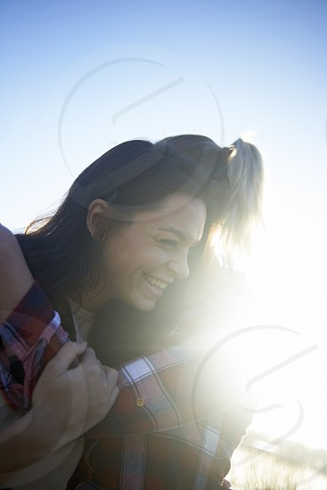 Young lesbian couple lovingly embracing each other in winter sunshine near a lake photo