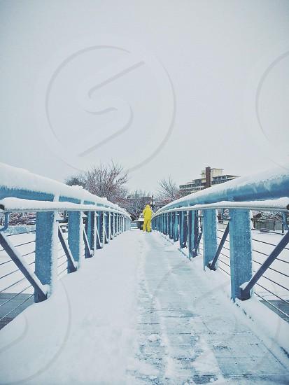 man in yellow rain coat on bridge photo