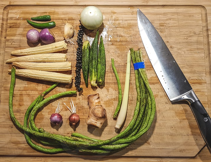 Close-up of fresh vegetables and kitchen knife on wooden desk photo