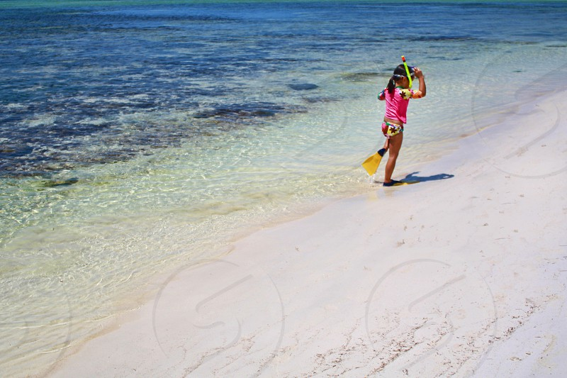 A little girl wearing a snorkel and flippers runs along the beach at the edge of a calm clear ocean. photo
