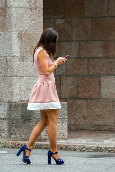 woman in blue and white mini dress wearing blue chunky heeled sandals holding smartphone during daytime photo