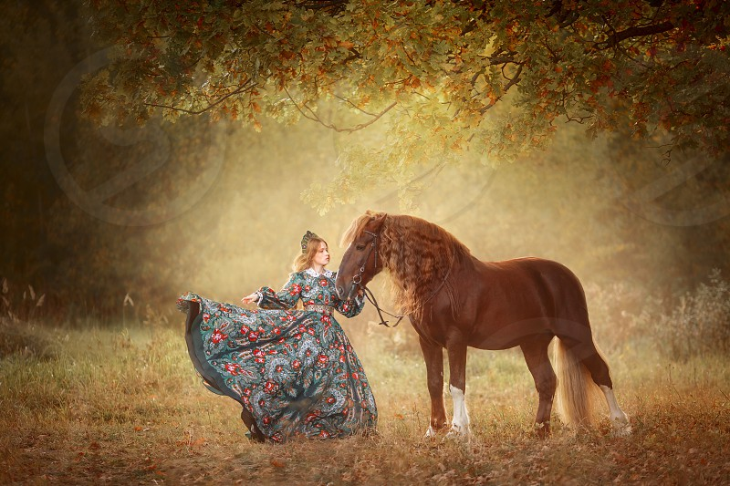 Beautiful young woman in Russian style dress with red horse photo