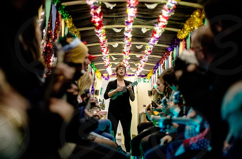 An entrepreneur woman instructing a group of coworkers on a canal boat how to play the ukulele. photo
