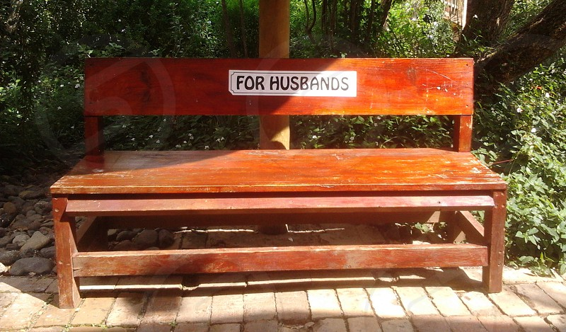 A bench outside a clothing store only for husbands. photo
