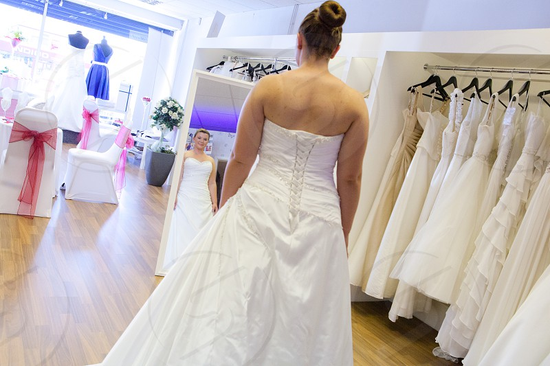 woman in weeding dress facing the mirror photo