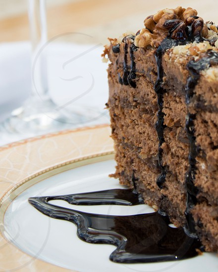 Mouthwatering chocolate cake with nuts on top and chocolate dressing. photo