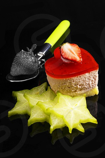 heart shaped strawberry cake dith star fruit or carambola decoration over black reflective backgound photo