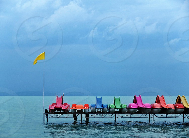 red orange blue green purple and yellow boats on dock near seawater below white clouds and blue sky at daytime photo